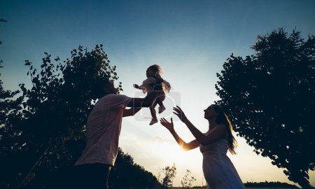 Photo for Parents and kid having fun spending time in garden - Royalty Free Image