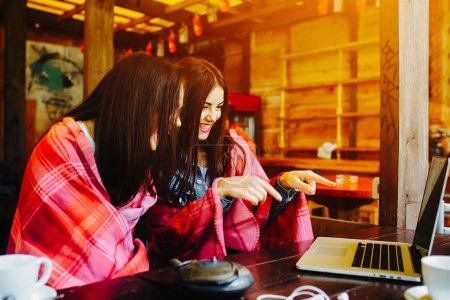 two girls watching something in laptop