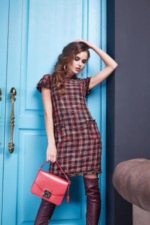 Photo pour Beauté femme dame habillée en sexy robe courte rouge fait tissus naturels collection élégante à la mode maquillage de cheveux longs, mode, style, intérieur chambre grise porte bleue tenant un accessoire sac en cuir - image libre de droit