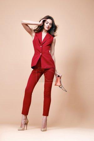 Photo pour Belle femme brune sexy porter veste de costume de soie rouge et pantalon vêtements de collection d'été pour femme d'affaires style de bureau décontracté tenir petite mousse marchandises sac faire une pose catalogue de modèles de mode . - image libre de droit