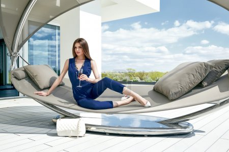 Brunette sexy woman glamour fashion luxury life style lady sit on stylish hammock modern interior building house party time drink champagne accessory lather bag summer blue sky nature resort success