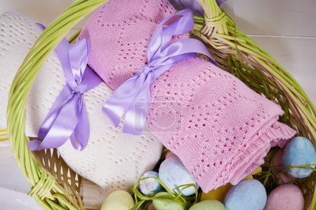Foto de Wicker basket Easter set with colored eggs hay crocheted blankets covered with silk satin ribbon easter holy celebration, happy. - Imagen libre de derechos