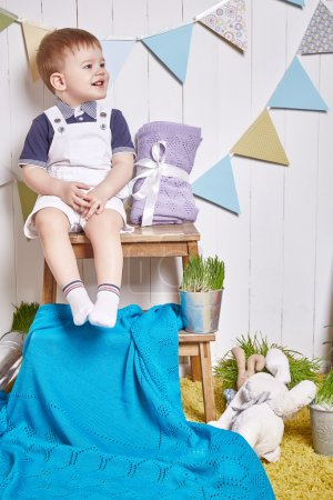 Foto de Beautiful little baby boy sitting on a chair with a knitted blanket Easter basket with colored eggs hay, Easter Bunny, a holy religious holiday, a happy guy cute child funny kid. - Imagen libre de derechos