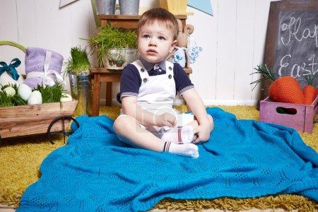Foto de Hermoso niño bebé sentado en una silla con una cesta de Pascua manta de punto con heno de huevos de colores, conejito de Pascua, una fiesta religiosa santo, un chico feliz niño lindo niño divertido niño feliz - Imagen libre de derechos