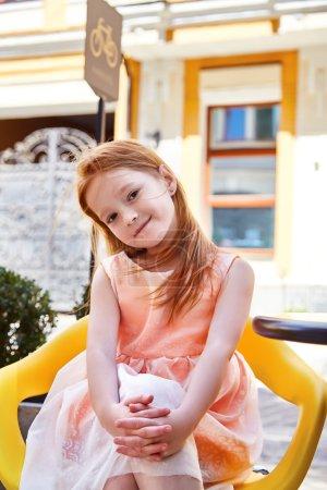 Beautiful little girl wear in fashion dress sitting in a cafe