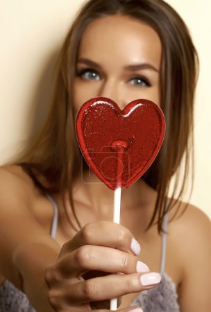 Beautiful young girl in a dressing gown of silk and lace with thin straps with a cut and bow in front of hands holding a lollipop in the shape of a red heart valentines day