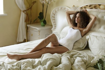 Young beautiful girl with curly hair lying on a bed with rumpled