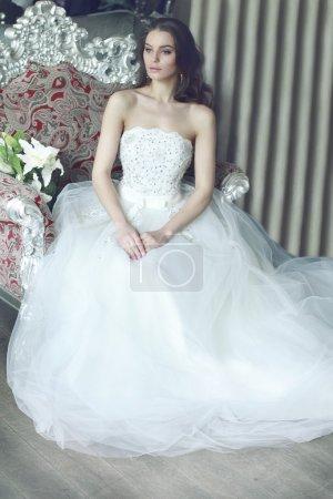Belle jeune mariée avec de longs cheveux bruns ondulés dans une robe de mariée blanche luxuriante en tulle, brodée de perles corset, noeud noué à la taille photographié à l'intérieur du restaurant