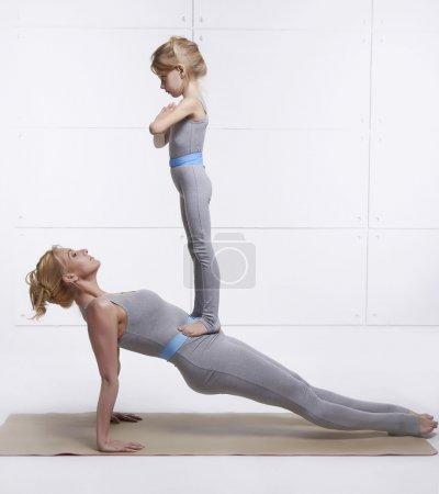 Photo pour Mère et fille faire des exercice d'yoga, fitness, gym, portant le même sport familiale confortable survêtements, sport femme appariés a mis ses mains sur l'enfant parole debout sur sa fille abdomen équilibrage - image libre de droit
