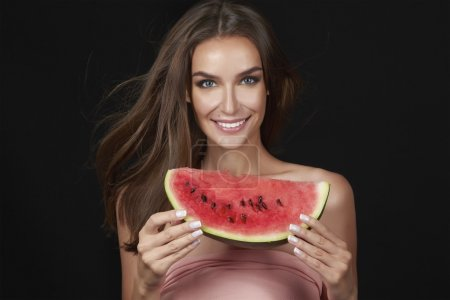 Beautiful sexy brunette woman eating watermelon on a white background, healthy food, tasty food, organic diet, smile healthy, black background passion