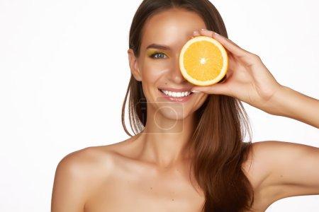 Photo pour Belle jeune femme sexy avec une peau saine parfaite et épaules nues de maquillage jour de longs cheveux bruns tenant pamplemousse orange citron saine alimentation perte de poids régime alimentaire des aliments biologiques - image libre de droit