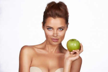 Photo for Young beautiful sexy girl with dark curly hair, bare shoulders and neck, holding big green apple to enjoy the taste and are dieting, healthy eating and organic foods, feeling temptation, smile, teeth - Royalty Free Image