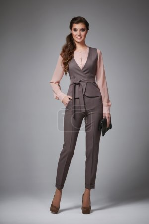 Beautiful sexy young business woman with evening make-up dressed in tight pants and silk blouse with lace long sleeves and high-heeled shoes small black handbag business clothes for meetings and walks