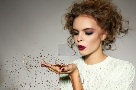 Photo for Beautiful sexy young blond girl with wavy hair bright evening make-up red lips long fluffy eyelashes holds palm with gold sequins in front of him and blows them a holiday New Year Christmas joy fun - Royalty Free Image