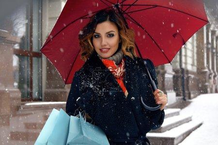 Beautiful woman snow street buy presents Christmas New Year