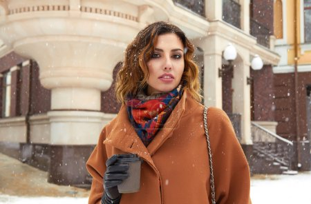 Photo pour Beautiful sexy young woman with curly brown hair with bright makeup wearing a brown coat goes on snow-covered street past the shops with a cup of hot coffee, cappuccino, tea, Christmas and New Year Winte - image libre de droit