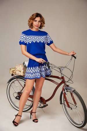 Beautiful sexy woman in short dress riding a bicycle