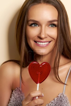Lovely woman smiling covers one eye lollipop red hear