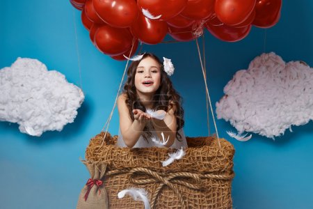 Photo for Small cute girl with beautiful face on a board with a lot of red balloons having heart form on  top flying in happy mood under bright blue sky with clouds and wind playing with her hair Valentines day - Royalty Free Image
