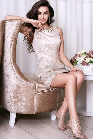 Photo for Beautiful sexy young brunette woman with long wavy hair thin slender figure perfect body and pretty face make-up wearing a beige evening skinny dress and jewelry - Royalty Free Image
