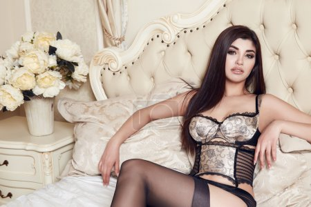Photo for Beautiful sexy long-haired brunette woman sitting on a bed with pillows in lace lingerie silk linens flower evening makeup perfect body shape - Royalty Free Image