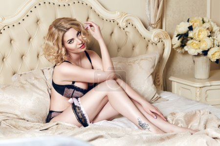 Photo for Beautiful sexy long-haired blonde woman sitting on a bed with pillows in lace lingerie silk linens flower evening makeup perfect body shape - Royalty Free Image