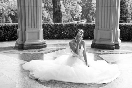 Beautiful young woman sexy brunette bride in a luxury white wedding dress the nature Castle Summer happiness awaits the groom before the wedding ceremony