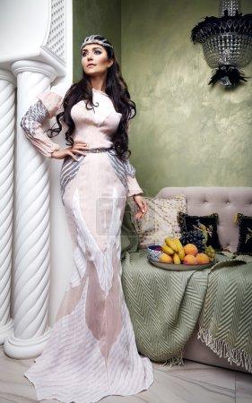 Photo pour Belle jeune femme sexy avec brunette de longs cheveux noirs et de la décoration en robe du soir de dentelle de soie, chambre à coucher en style marocain velours oreillers luxueux mobilier mode Sarouel concubine fruits - image libre de droit
