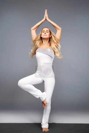 Beautiful young sexy woman with perfect athlete blond healthy slim figure is engaged in gymnastics exercise stretching, trainers, trainer, fitness, sports, health wear casual sports clothes in gym