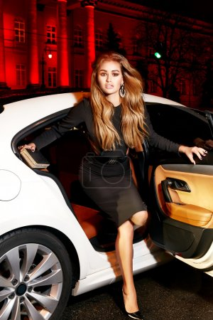 Beautiful young sexy blonde wearing evening makeup in elegant fitting dress fashionable stylish sitting in cabin of expensive car