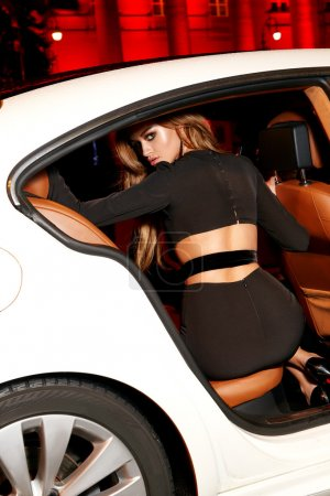 Beautiful young sexy blonde  sitting in cabin of expensive car