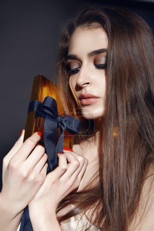 Photo pour Portrait d'une belle jeune fille sexy maquillage lumineux pour la soirée, brune aux cheveux longs, tenant une boîte cadeau en or arc en soie, surprise, vacances du jour de naissance des amoureux de la Saint-Valentin - image libre de droit