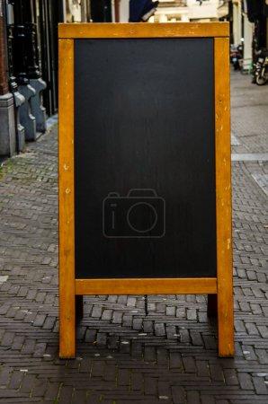 Empty Chalkboard on City Street