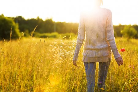 Young woman walking in the field toward the sun holding a poppy flower.