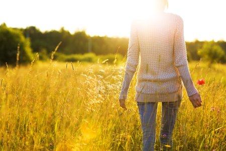 Photo pour Jeune femme marchant dans le champ vers le soleil tenant une fleur de pavot . - image libre de droit