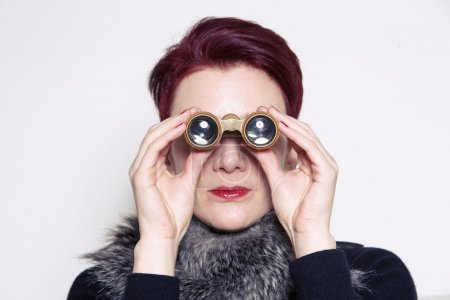 Woman with red hair looking through binoculars