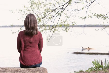Photo for Backside of brunette young woman sitting on tree in front of a lake - Royalty Free Image