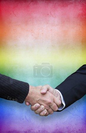 Photo pour Gros plan de poignée de main avec les couleurs de l'arc-en-ciel pour la fierté gay - image libre de droit