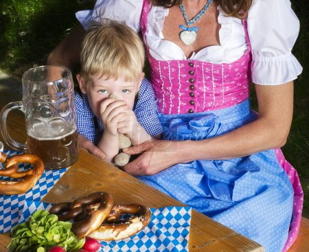 Photo for Little bavarian blond boy sits next to his mother - Royalty Free Image