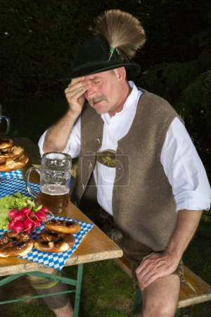 Photo for Bavarian man sitting on bench with a beer mug and is drunk - Royalty Free Image