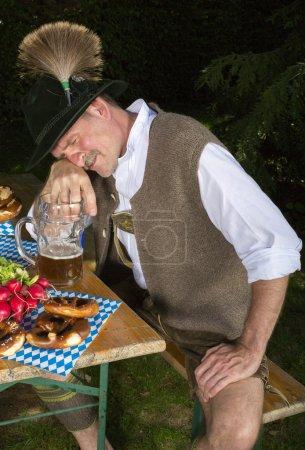 Photo pour Bavarois homme assis sur le banc avec une tasse de bière et est ivre - image libre de droit