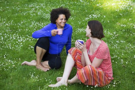 Photo for Two women sitting on a blanket on grass holding cups in their hands - Royalty Free Image