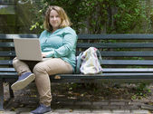young woman in park with laptop