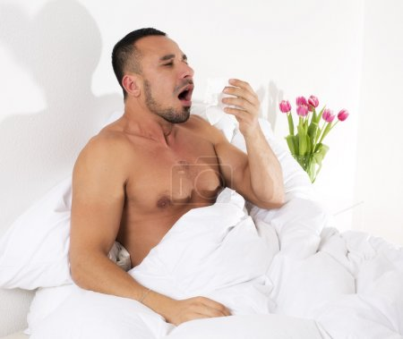 Man in bed with a cold