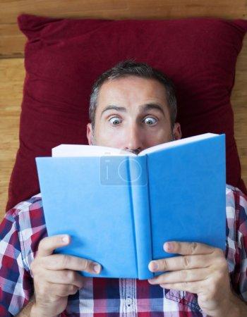 Photo pour Homme couché sur le sol et lisant un livre - image libre de droit