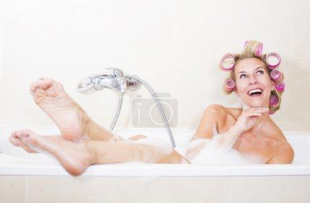 Photo pour Femme blond s'asseyant dans la baignoire avec des curlers dans son cheveu - image libre de droit
