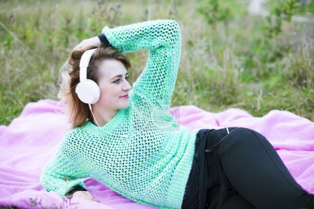 Photo for Young woman laying on a pink blanket with headphones on - Royalty Free Image