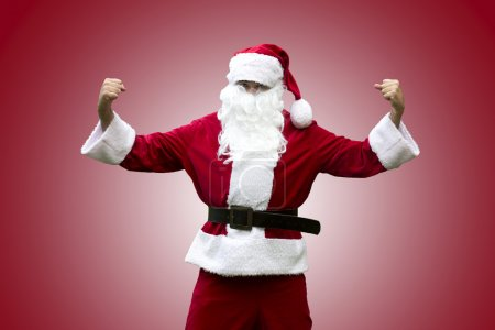 Photo for Santa Claus standing and flexing his muscles - Royalty Free Image