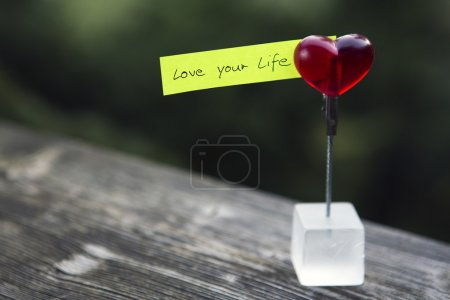 """Photo for Handwritten quote """"love your life"""" on paper clipped on a heart - Royalty Free Image"""