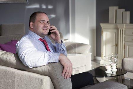 Photo pour Gros homme en chemise et cravate se trouve sur le canapé et parle au téléphone - image libre de droit